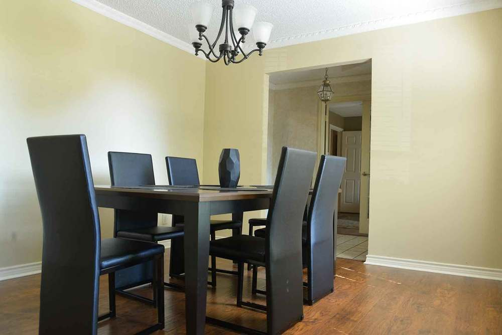 The black dining room set in the main living room at our NE Dallas sober house
